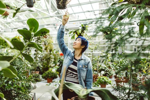 Student reaching for a plant in campus greenhouse, with expression of wonder